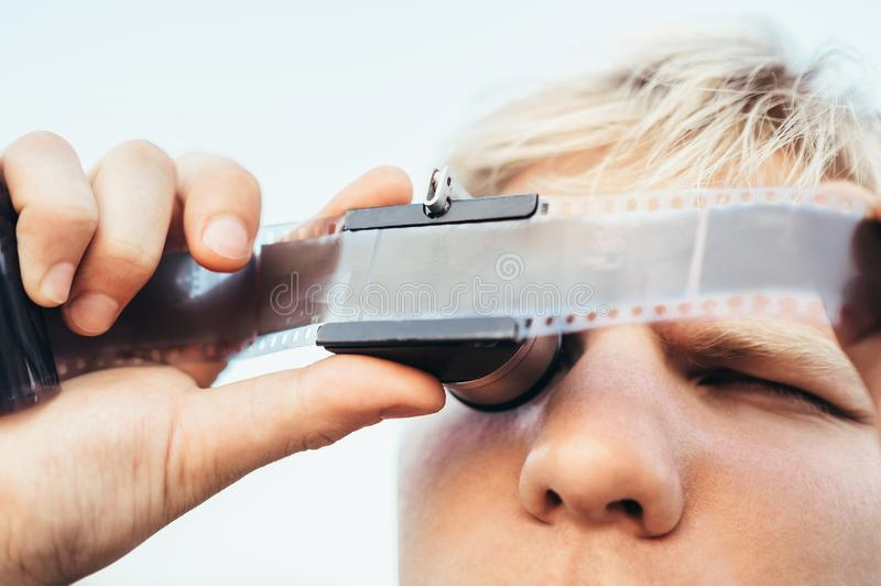 Male uses the Old vintage 35mm film Negative Viewer to see a frames on the vintage camera slides. through magnifier. stock photo