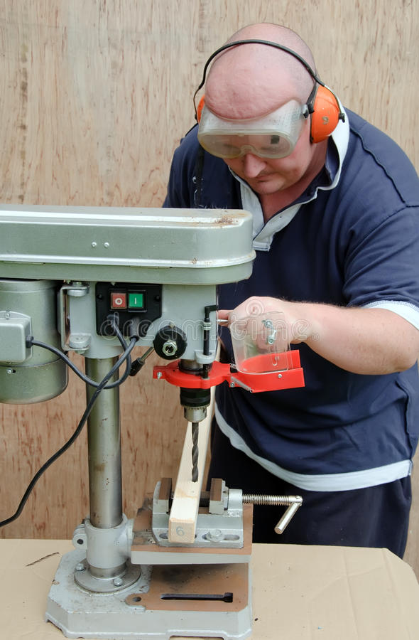 Male Using A Drill Press On Wood Stock Photo