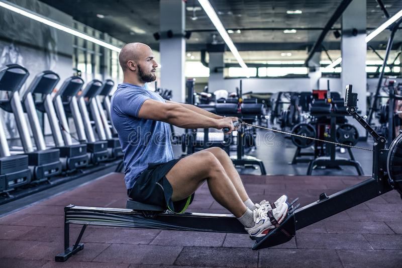 Male using rowing machine at fitness club. Young man doing exerc stock photos