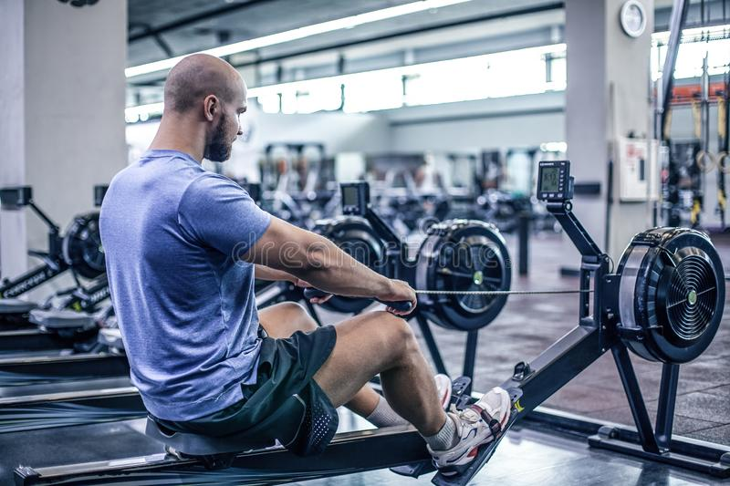 Male using rowing machine at fitness club. Young man doing exercises on fitness machine in gym. Side view stock images