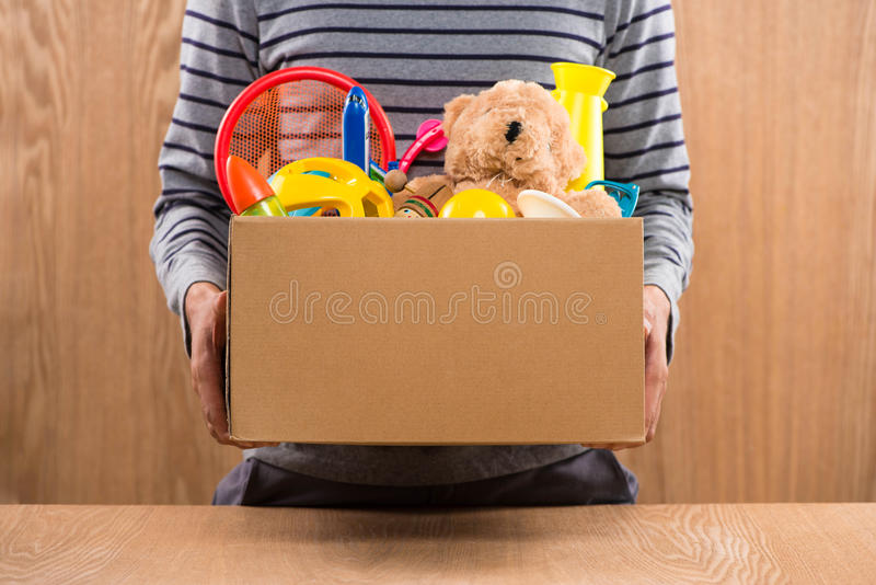 Male volunteer holding donation box with old toys. stock image