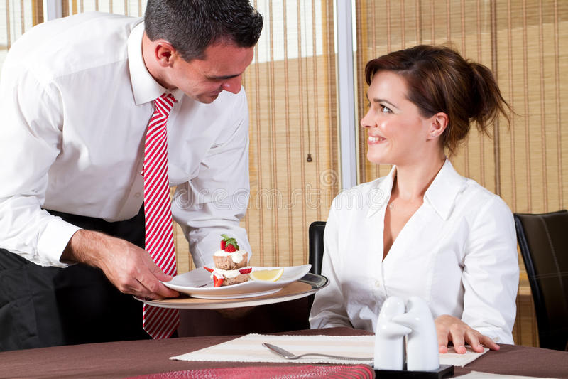 Male waiter brings dessert. Friendly male waiter brings to the customer the ordered dessert royalty free stock photography