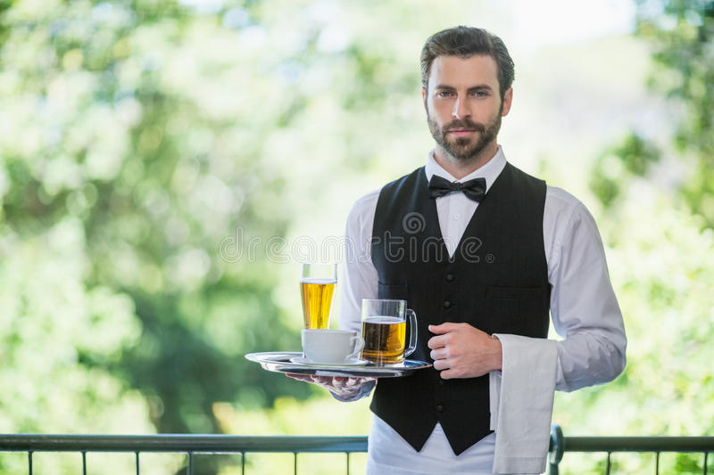 Male waiter holding tray with beer glass and coffee cup in restaurant royalty free stock images