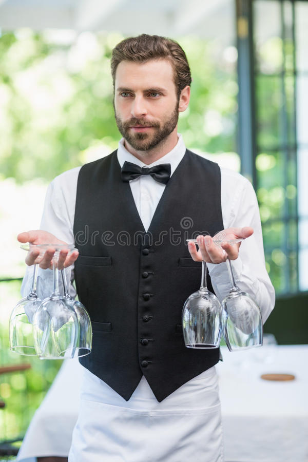 Male waiter holding wine glasses in the restaurant royalty free stock photo