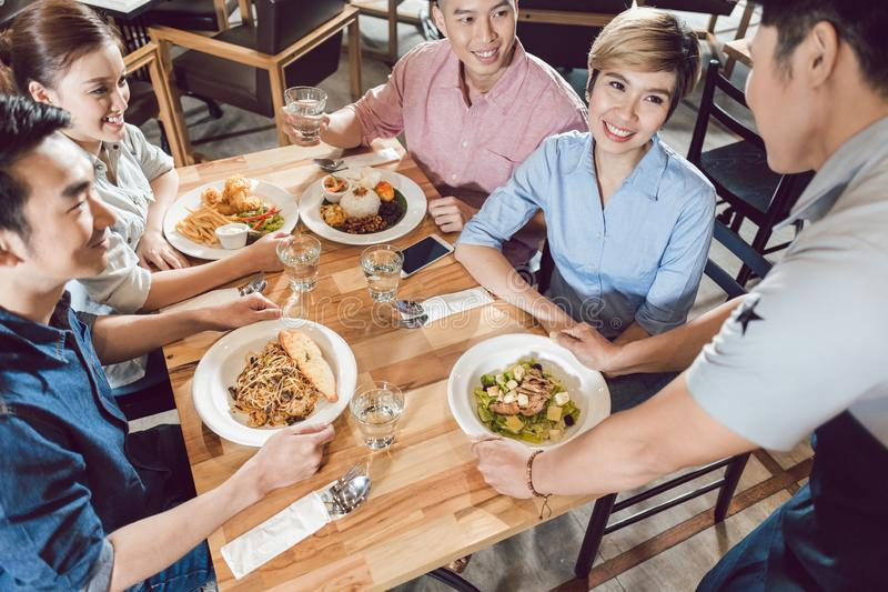 Male waiter serving food on table stock images