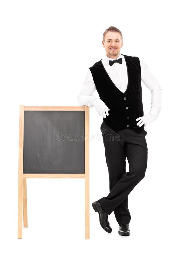 Male waiter standing next to a blackboard stock photo