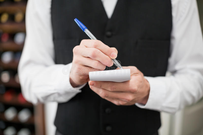 Male waiter taking down order in the restaurant royalty free stock photo
