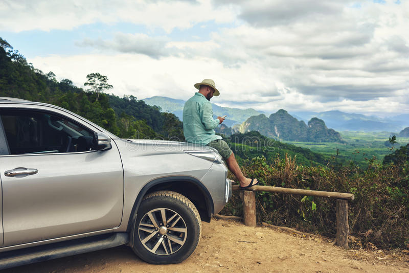 Male wanderer is watching video on cell telephone during trip on suv in Latin America. Young hipster guy is chatting on mobile phone, while is sitting on stock images