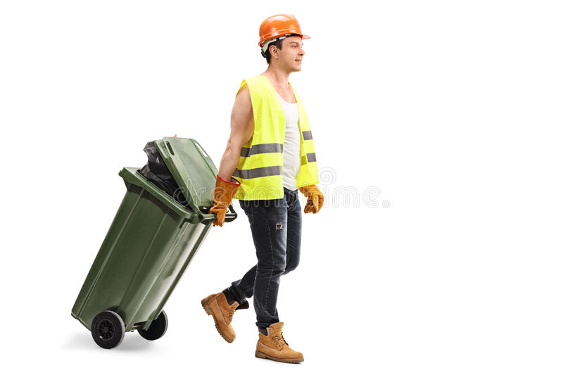 Male waste collector dragging a trash can. Full length portrait of a male waste collector dragging a trash can isolated on white background stock images