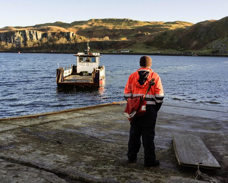 Male wearing working clothes standing on the pier with a boat taking off stock photo