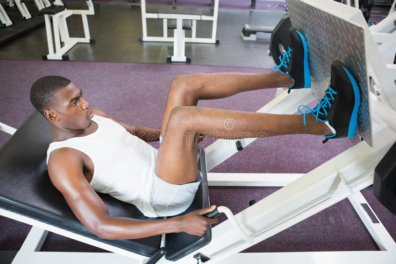 Male weightlifter doing leg presses in gym. Side view of male weightlifter doing leg presses in gym stock photo