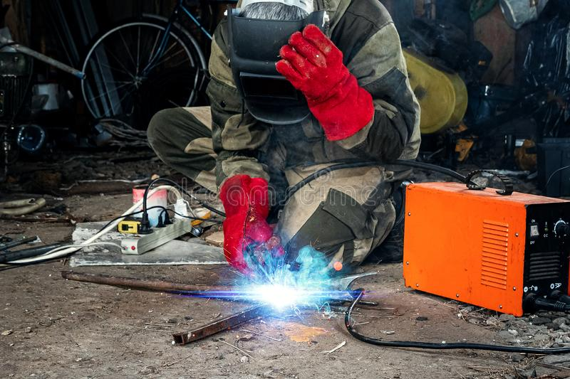 A male welder in a welding mask works with an arc electrode in his garage. Welding, construction, metal work stock photos