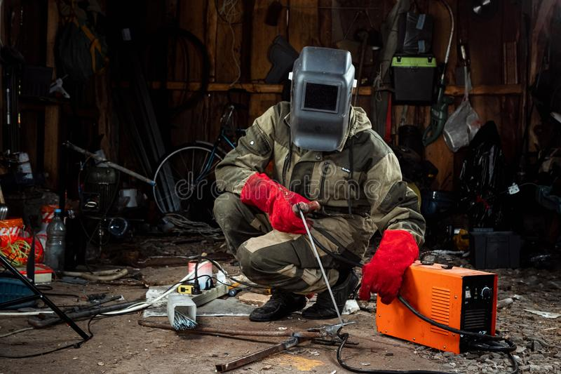 A male welder in a welding mask works with an arc electrode in his garage. Welding, construction, metal work royalty free stock photography