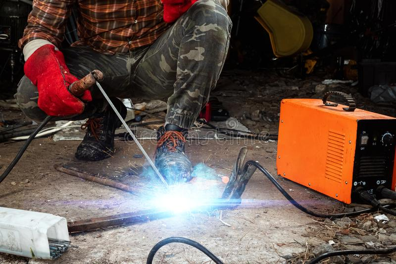 A male welder in a welding mask works with an arc electrode in his garage. Welding, construction, metal work stock image