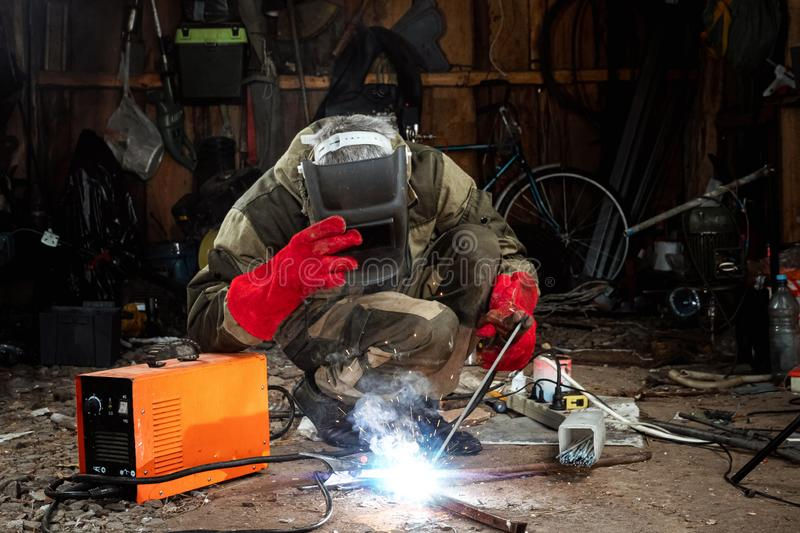 A male welder in a welding mask works with an arc electrode in his garage. Welding, construction, metal work stock photography