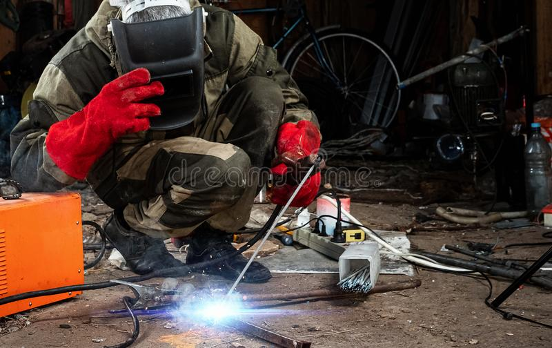 A male welder in a welding mask works with an arc electrode in his garage. Welding, construction, metal work royalty free stock photos