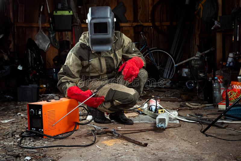 A male welder in a welding mask works with an arc electrode in his garage. Welding, construction, metal work royalty free stock images