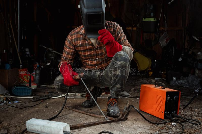 A male welder in a welding mask works with an arc electrode in his garage. Welding, construction, metal work stock images