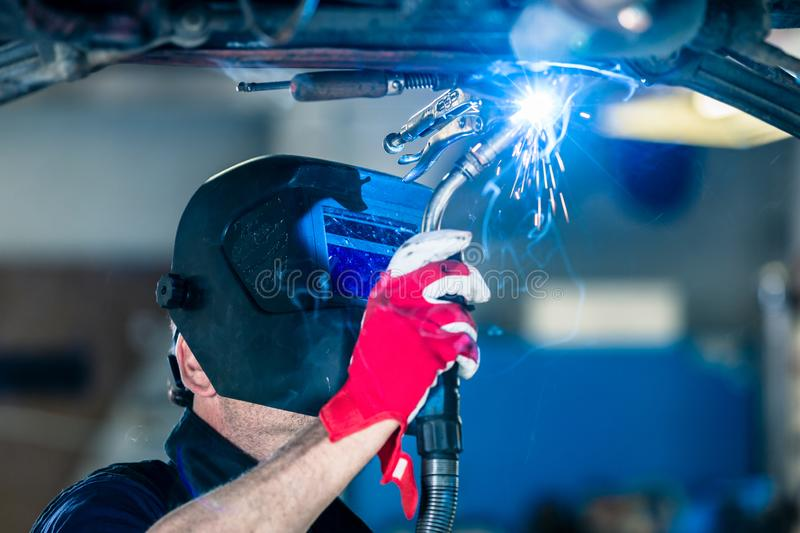Male welds the automotive part in car factory. With sparks royalty free stock image