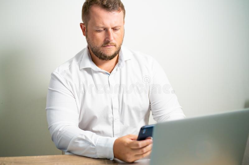 Male in white shirt looks into the phone at the workplace sitting at a table near the computer.  stock photos