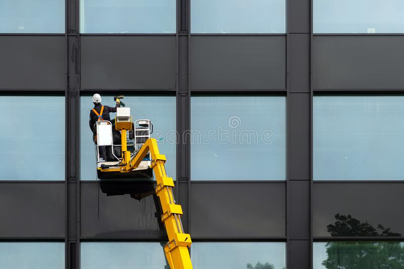 Male window cleaner cleaning glass windows on modern building high in the air on a lift platform. Worker polishing glass high in stock photo
