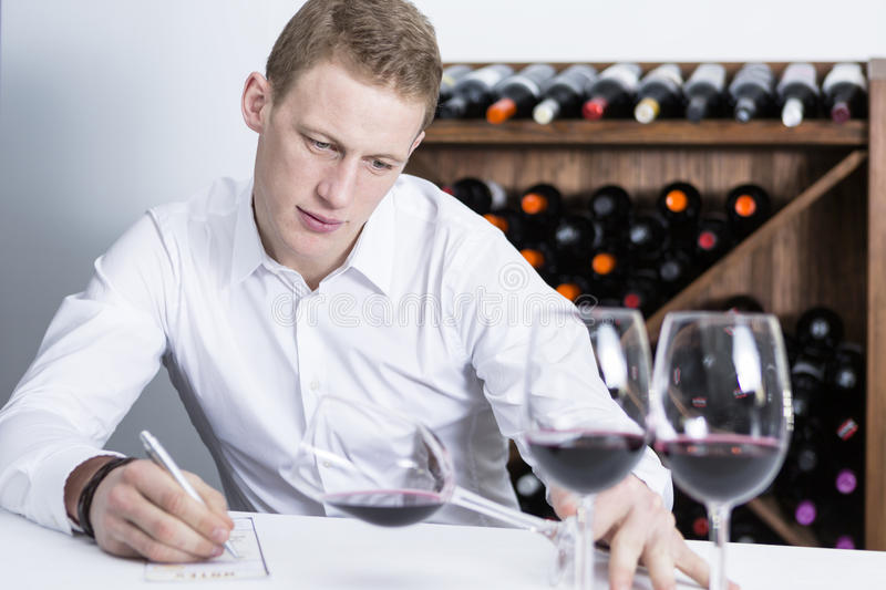 Male winemaker examining a wine glass. Young man on a wine tasting session on the visual phase is writing down in a wine tasting sheet at a restaurant stock photos