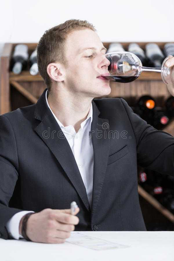 Male winemaker tasting a red wineglass. Man on a wine tasting session on the gustatory phase tasting the red wine is writing down in a wine tasting sheet at a royalty free stock photography