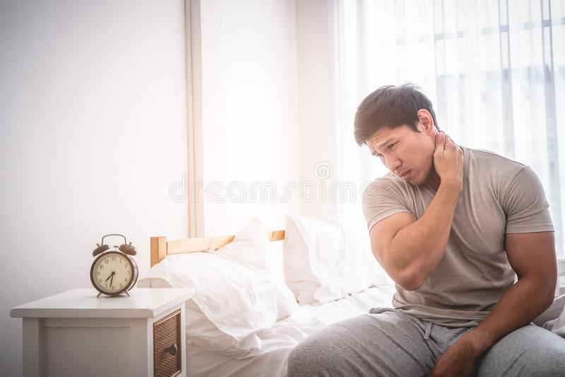 Male woke up by alarm clock having neck pain stock photos