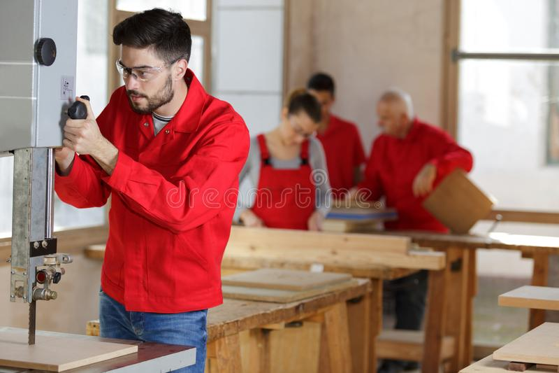 Male woodworker adjusting band saw setting. Adjusting royalty free stock photos