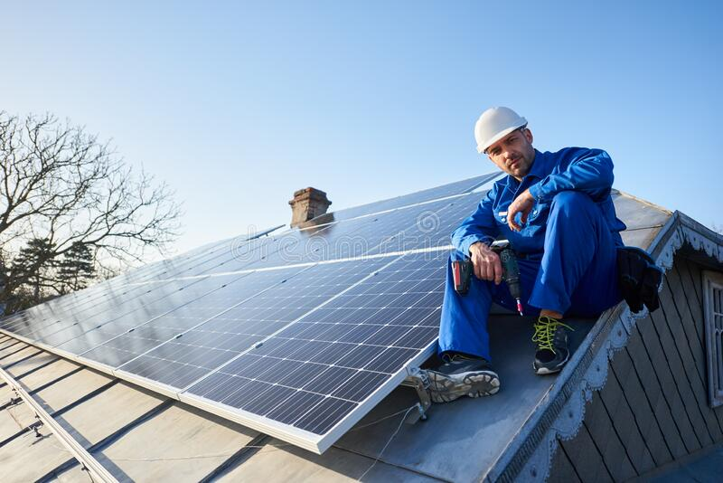 Electrician mounting solar panel on roof of modern house. Male worker in blue suit and protective helmet installing stand-alone solar photovoltaic panel system stock photo