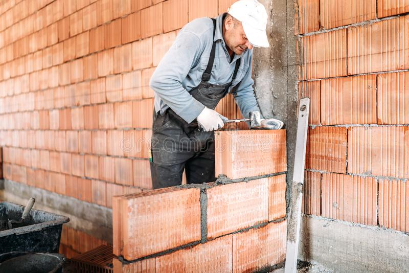 Male worker, bricklayer. Professional worker building house stock photography