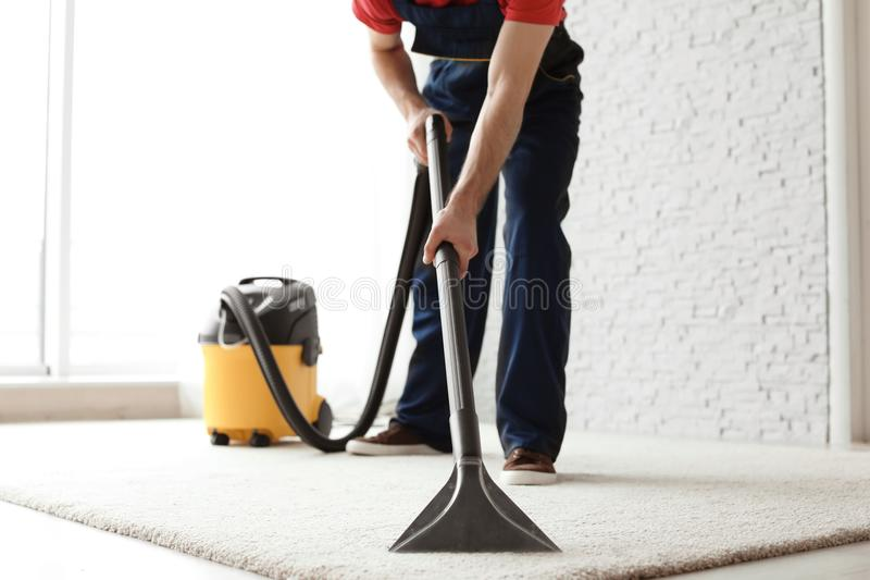 Male worker cleaning carpet with vacuum royalty free stock photo