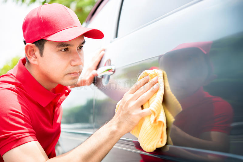 Male worker cleaning and looking at car door seriously royalty free stock images