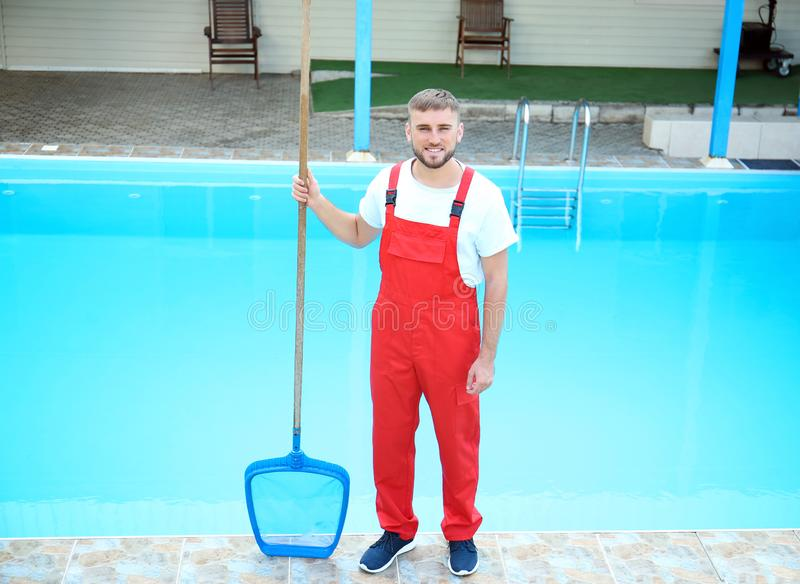 Male worker cleaning outdoor pool. With scoop net royalty free stock image