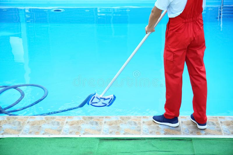 Male worker cleaning outdoor pool stock images