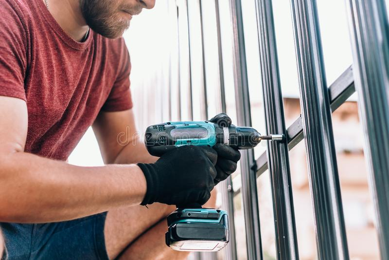 male worker with cordless screwdriver power tool fastening screws royalty free stock photography