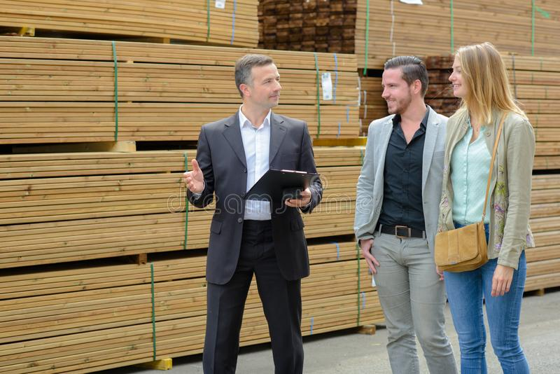 Male worker and couple choosing planks stock photo