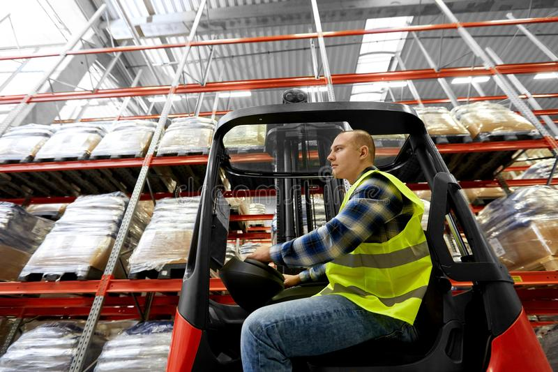 Male worker driving forklift loader at warehouse royalty free stock images