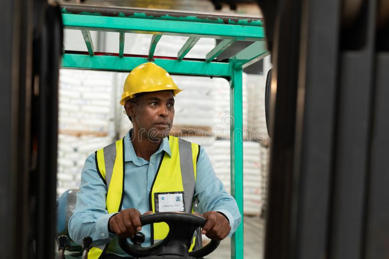 Male worker driving forklift in warehouse. Front view of male worker driving forklift in warehouse. This is a freight transportation and distribution warehouse stock photography