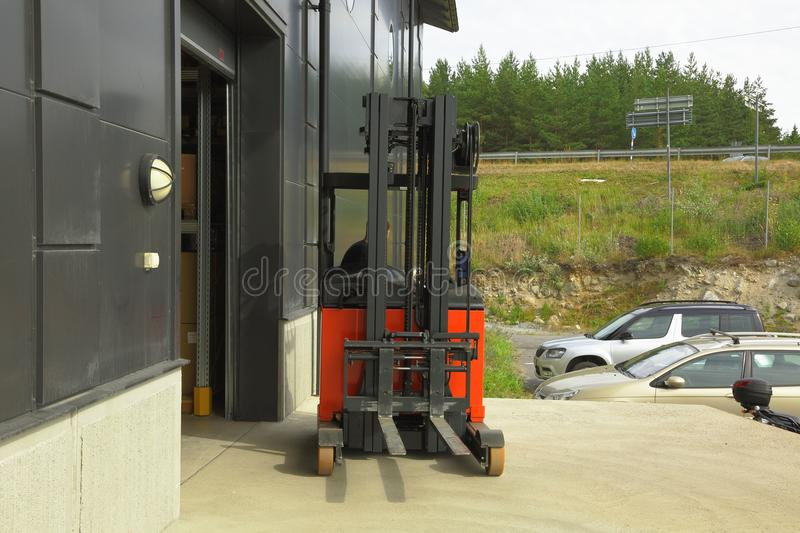 Male worker driving out of a warehouse on the fork-lift-truck royalty free stock images