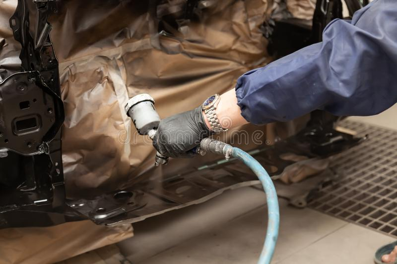 A male worker in jumpsuit and gloves paints with a spray gun a front frame part of the car body in black after being damaged at an royalty free stock images