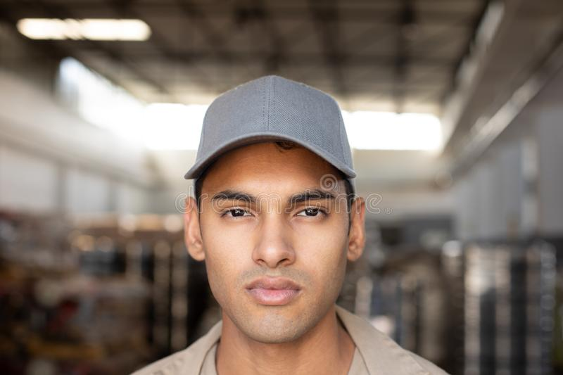 Male worker looking at camera in warehouse. Close-up of male worker looking at camera in warehouse. This is a freight transportation and distribution warehouse stock photo