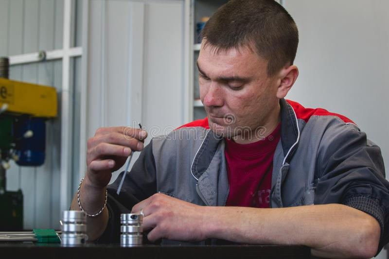Male worker manually assembles metal detail for CNC machine at factory with lathes stock images