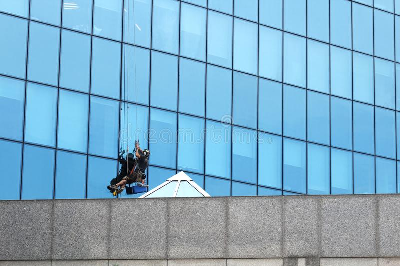 Male worker in overalls professional repair the windows in high-rise. Worker washing windows in office building. Washer wash the. Male worker in overalls stock photo