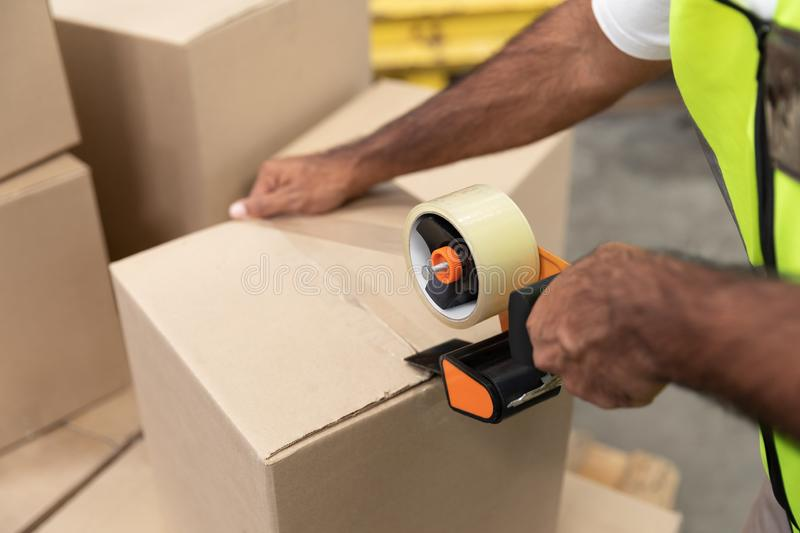 Male worker packing cardboard box with tape gun dispenser in warehouse royalty free stock image