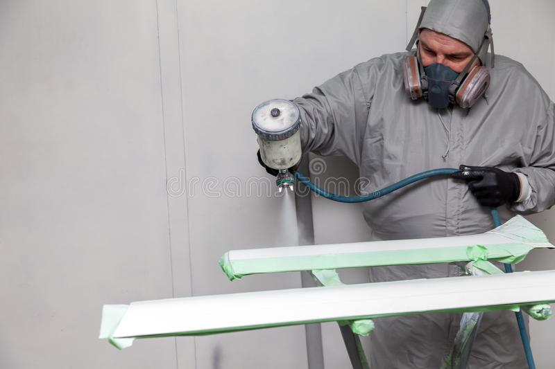 A male worker paints with a spray gun a part of the car body in silver after being damaged at an accident. Plastic elements from royalty free stock images