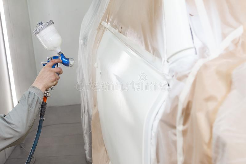 A male worker paints with a spray gun a part of the car body in white after being damaged at an accident. Door from the vehicle royalty free stock photo