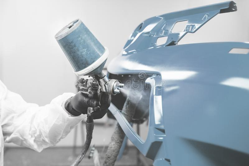 Male worker in protective clothes and mask painting car bumper using spray paint. Body repair of the vehicle after the accident stock images