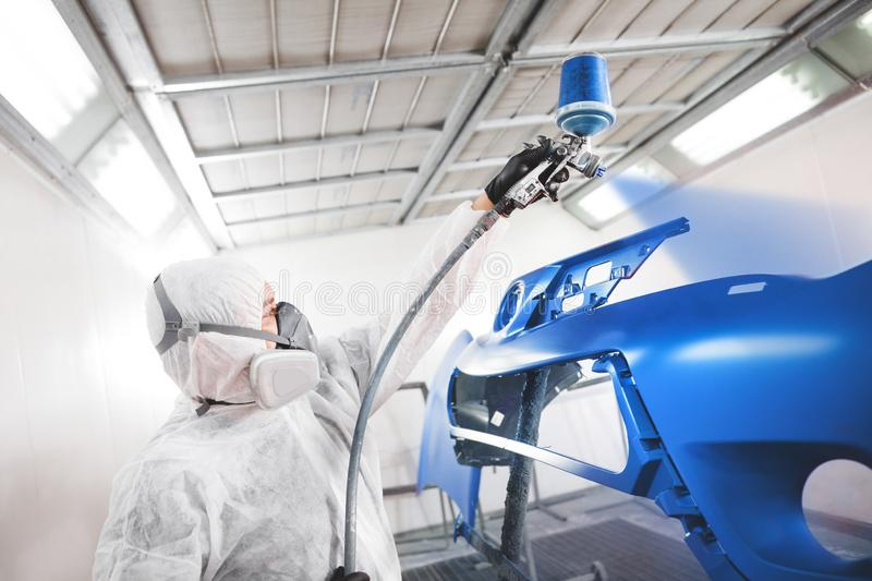 Male worker in protective clothes and mask painting car bumper using spray paint. Body repair of the vehicle after the accident royalty free stock photography