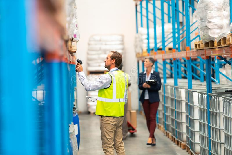 Male worker scanning package with barcode scanner in modern warehouse royalty free stock images